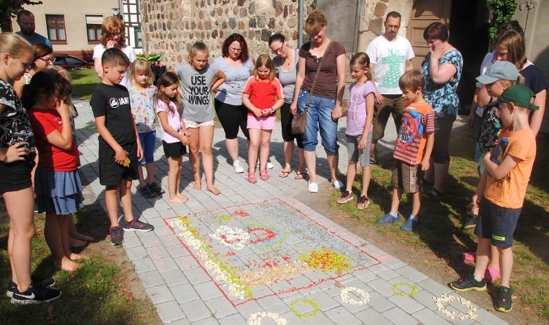 Kinder gestalten Blumenweg mit bunten Steinen